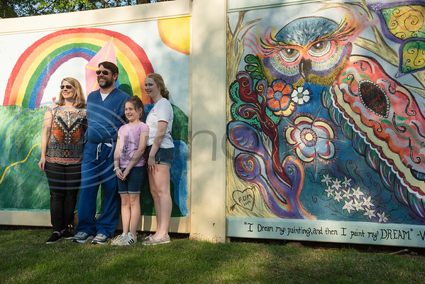 Allison Harrell, 11, has her photo taken with her family, Melissa Harrell, Bruce Harrell and sister KellyAnn Harrell, 14, in front of the mural she painted at the grand re-opening of Hillside Park in Tyler on Tuesday April 9, 2019. Hillside Park has undergone extensive renovations that include the installations of new sidewalks, lights, bathrooms, tables, benches, playground equipment and an art wall featuring the work of 15 local artists.   (Sarah A. Miller/Tyler Morning Telegraph)