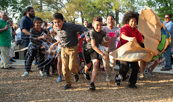 Children run through a banner to the playground at the grand re-opening of Hillside Park in Tyler on Tuesday April 9, 2019. Hillside Park has undergone extensive renovations that include the installations of new sidewalks, lights, bathrooms, tables, benches, playground equipment and an art wall featuring the work of 15 local artists.   (Sarah A. Miller/Tyler Morning Telegraph)