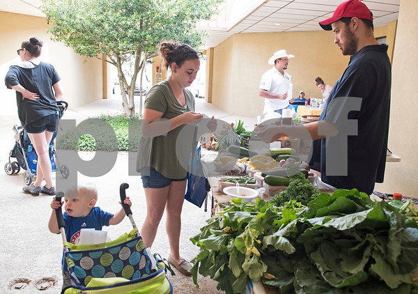 WIC client Courtney Rodgers uses a voucher to purchase vegetables for her son Koda, 1, and herself from farmer Cody Neal Carter of the East Texas State Fair Farmer's Market outside of the WIC office on Amherst in Tyler May 11, 2017. The public is invited to use cash. Beginning Thursday, May 11th, and running every Thursday morning until July 27th, NET Health is operating the Farmers Market & Block Party at both of the Tyler NET Health WIC locations - 815 North Broadway and 225 East Amherst.  Each event will be held every Thursday morning from 8:30 a.m. until 12:00 p.m.  (Sarah A. Miller/Tyler Morning Telegraph)