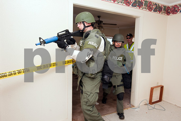 photo by Sarah A. Miller   Tyler Police SWAT team members train for the worst-case scenario of entering a home Thursday April 11 in Tyler. The team wore their full gear and used simunition guns to complete various exercises inside of a house used for training.
