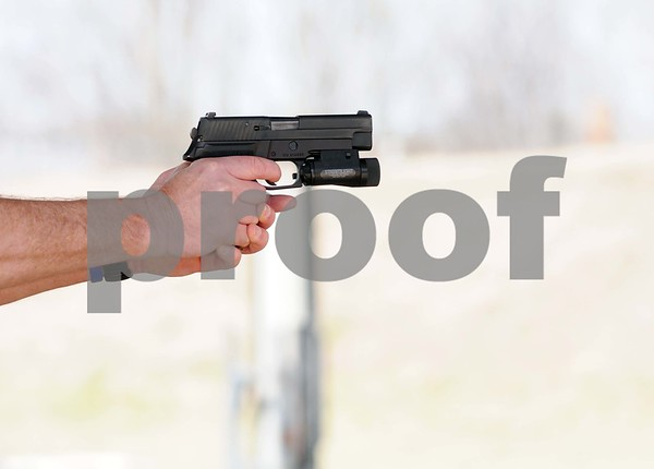 photo by Sarah A. Miller/Tyler Morning Telegraph  Tyler Morning Telegraph reporter Kenneth Dean is trained by Tyler Police Department SWAT members on a Sig Sauer .357 handgun Thursday at the police department gun range in Tyler. Dean learned the ins and outs of SWAT training through physical training, the gun range and a video simulation.
