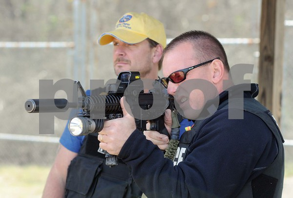 photo by Sarah A. Miller/Tyler Morning Telegraph   Tyler Police Department SWAT member Sergeant David Hall trains Tyler Morning Telegraph reporter Kenneth Dean on using a AR15 rifle Thursday at the police department gun range in Tyler. Dean learned the ins and outs of SWAT training through physical training, the gun range and a video simulation.