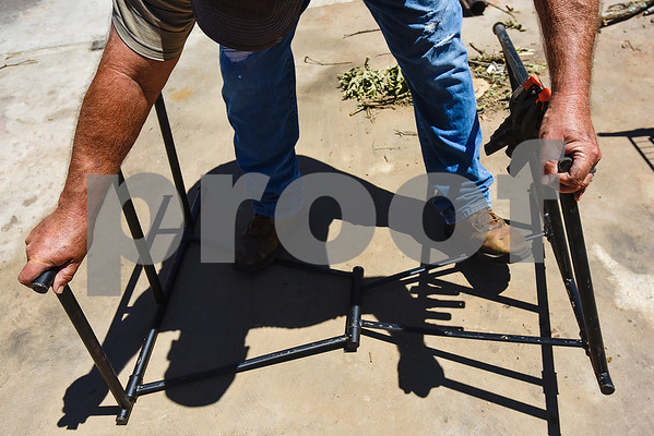 Bill Cobb works to bend part of a shelf back into place as he helps his friend Bill Cockrum pick up his shop after a tornado in Fruitvale, Texas, on Monday, May 1, 2017. Four confirmed tornadoes ranging from EF-0 to EF-3 touched down in Northeast Texas April 29, causing widespread damage and power outages. (Chelsea Purgahn/Tyler Morning Telegraph)