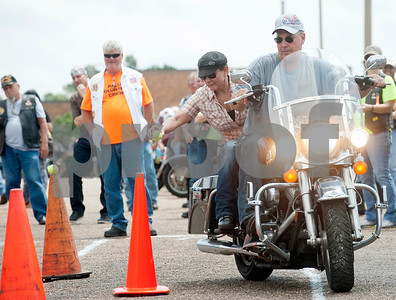 Kevin Meadows and Gisela Macedo of Allen compete in a ball and cone motorcycle game during the 2015 Texas State Harley Owners Group Rally held at Harvey Convention Center in Tyler Saturday. Macedo had to pick up six tennis balls from the tops of the cones then place the balls back on another set of cones as Meadows drove.  (photo by Sarah A. Miller/Tyler Morning Telegraph)