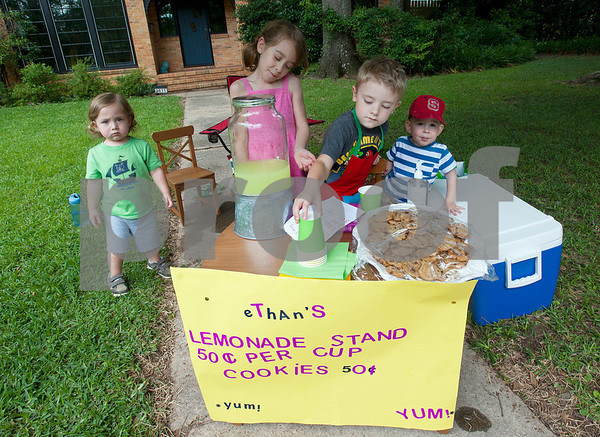 Ashton Reese, 1, Autumn Hanna, 6, Ethan Reese, 6, and Benjamin Hanna, 1, work selling cookies and drinks at their lemonade stand on College Ave. in Tyler Saturday.   (photo by Sarah A. Miller/Tyler Morning Telegraph)