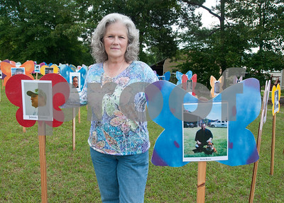 Pamela Pickett stands next to the wooden butterflies bearing her son's names and photographs at the Compassionate Friends Butterfly Release Saturday. Butterflies were released in memory children who have died at any age at the Compassionate Friends Butterfly Release Saturday, May 16, 2015 at the Sharon Shrine Temple, 10027 State Highway 31 East in Tyler.   (photo by Sarah A. Miller/Tyler Morning Telegraph)