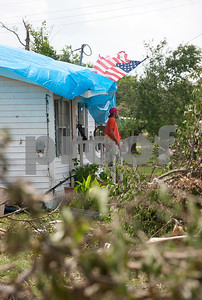 Mitch Ritchie, 50, stands on his doorstep under a surprisingly intact American flag at his home on Bois d' Arc Street in Van Thursday May 15, 2015. Bois d' Arc Street in Van was hit by a tornado, and many of the neighboring homes were completely destroyed. Ritchie says he was amazed that his flag was still flying after the severe storm.   (photo by Sarah A. Miller/Tyler Morning Telegraph)