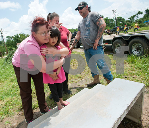 "Laura White consoles her granddaughter Mariah Mendoza, 7, on the front steps of her daughter Angela Reed's destroyed home in Van Thursday May 15, 2015 along with Reed and father-in-law Robert White. The Van tornado destroyed both family homes which were both located on Bois d' Arc Street in Van. All that remains of Angela Reed and her husband Chase Scruggs' home is the front steps. ""We're never going to leave Van,"" Robert White said.  (photo by Sarah A. Miller/Tyler Morning Telegraph)"