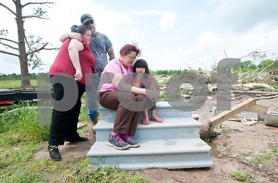 "Angela Reed, left, is hugged by her father-in-law Robert White while Laura White consoles Reed's daughter Mariah Mendoza, 7, on the front steps of Angela Reed's destroyed home in Van Thursday May 15, 2015. The Van tornado destroyed both family homes which were both located on Bois d' Arc Street in Van. All that remains of Angela Reed and her husband Chase Scruggs' home is the front steps. ""We're never going to leave Van,"" Robert White said.  (photo by Sarah A. Miller/Tyler Morning Telegraph)"