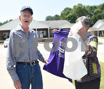 Barbara Stephens shows her brother Jim Benton a free t-shirt he received from The Smith County Adult Protective Services Board Friday during their door-to-door campaign for elder abuse awareness month in Lindale May 6, 2016.  (Sarah A. Miller/Tyler Morning Telegraph)