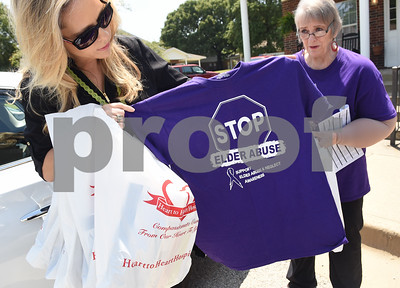 Sharon Brown, vice president of The Smith County Adult Protective Services Board, and Legends of Lindale independent living manager Sue North, right, give out informational packets and t-shirts on a door-to-door campaign for Elder Abuse Awareness Month.   (Sarah A. Miller/Tyler Morning Telegraph)