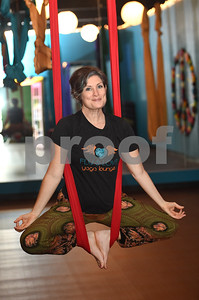 Beth Lytle, owner of Fly and Love Yoga Lounge, sits in one of 11 aerial yoga swings inside the studio, 17968 FM 2493 in Flint. Fly and Love includes a large lounge area complete with free Wi-Fi, coffee, tea and juice for purchase, coloring books, local art and items for sale from the fair trade Come Together Trading Company.   (Sarah A. Miller/Tyler Morning Telegraph)