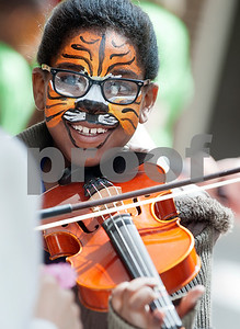 Caldwell Elementary Student Janiah McGee, 9, gets a five minute violin lesson after have her face painted as a tiger during the Tyler ISD ArtsFest held Saturday at Harvey Hall in Tyler. The event was hosted by the Tyler ISD Visual and Performing Arts Department and  featured artwork from students as well as arts and crafts activities and  live choir, band, orchestra and dance performances.  (photo by Sarah A. Miller/Tyler Morning Telegraph)