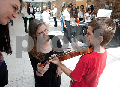 "Tanya Merritt of Tyler, left, watches as Hubbard Middle School orchestra teacher Lisa Lininger helps her son Coleman Merritt with a five minute violin lesson during the Tyler ISD ArtsFest held Saturday at Harvey Hall in Tyler. ""This is the first time he has played an instrument,"" Tanya Merritt said. Coleman Marritt is a student at Jack Elementary School. The event was hosted by the Tyler ISD Visual and Performing Arts Department and  featured artwork from students as well as arts and crafts activities and  live choir, band, orchestra and dance performances.  (photo by Sarah A. Miller/Tyler Morning Telegraph)"