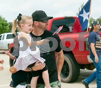 Jason Bruney of Tyler and his daughter Ella Bruney, 3, gather at the Village at Cumberland Park for the East Texas Flag Coalition ride on Broadway Ave. from the Village at Cumberland Park to T.B. Butler Fountain Square in downtown Tyler, Texas Saturday May 23, 2015. Over 30 vehicles participated in the East Texas Flag Coalition ride. The East Texas Flag Coalition is a patriotic group that aims to visibly show their American pride by places flags on trucks, cars and motorcycles during their community rides.  (photo by Sarah A. Miller/Tyler Morning Telegraph)