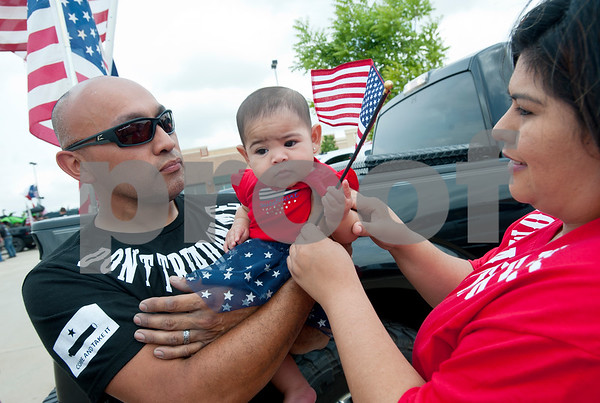 John Resendiz of Tyler holds his six-month-old daughter Enily as his wife Lolly Resendiz hands her an American flag to wave as they gather to drive their truck in East Texas Flag Coalition ride on Broadway Ave. from the Village at Cumberland Park to T.B. Butler Fountain Square in downtown Tyler, Texas Saturday May 23, 2015. Their truck was one of over 30 vehicles participating in the East Texas Flag Coalition ride. The East Texas Flag Coalition is a patriotic group that aims to visibly show their American pride by places flags on trucks, cars and motorcycles during their community rides.  (photo by Sarah A. Miller/Tyler Morning Telegraph)
