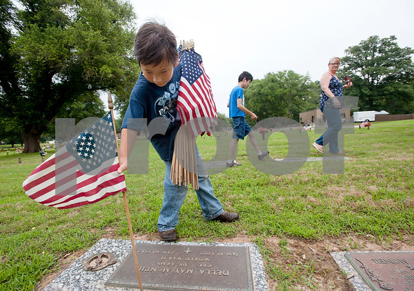Boy Scout Cameron Collins, 10, of Whitehouse, places a flag by a veteran's headstone at Tyler Memorial Funeral Home Cemetery and Mausoleum Saturday morning. Scout troops planted hundreds of American flags on the head stones of veterans Saturday at Tyler Memorial Funeral Home Cemetery and Mausoleum in preparation for Memorial Day Monday. The cemetery will be hosting a Memorial Day service open to the public at 11 a.m.  (photo by Sarah A. Miller/Tyler Morning Telegraph)