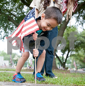 Jonah Benitez, 4, of Tyler, places a flag on a veteran's headstone at Tyler Memorial Funeral Home Cemetery and Mausoleum Saturday morning along with his two brothers, a Cub Scout and Boy Scout in troop 335. Scout troops planted hundreds of American flags on the head stones of veterans Saturday at Tyler Memorial Funeral Home Cemetery and Mausoleum in preparation for Memorial Day Monday. The cemetery will be hosting a Memorial Day service open to the public at 11 a.m.  (photo by Sarah A. Miller/Tyler Morning Telegraph)