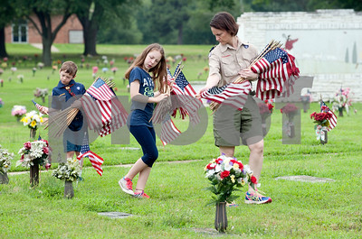 Cub Scout pack 370 leader Lisa Curvow, her daughter Katie Curvow, 11, and son Lane Curvow, 8, carry a large number of American flags as they look for veterans' headstones at Tyler Memorial Funeral Home Cemetery and Mausoleum Saturday morning. Scout troops planted hundreds of American flags on the head stones of veterans Saturday at Tyler Memorial Funeral Home Cemetery and Mausoleum in preparation for Memorial Day Monday. The cemetery will be hosting a Memorial Day service open to the public at 11 a.m.  (photo by Sarah A. Miller/Tyler Morning Telegraph)