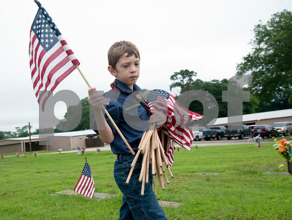 Scout troops planted hundreds of American flags on the head stones of veterans Saturday at Tyler Memorial Funeral Home Cemetery and Mausoleum in preparation for Memorial Day Monday. The cemetery will be hosting a Memorial Day service open to the public at 11 a.m.  (photo by Sarah A. Miller/Tyler Morning Telegraph)
