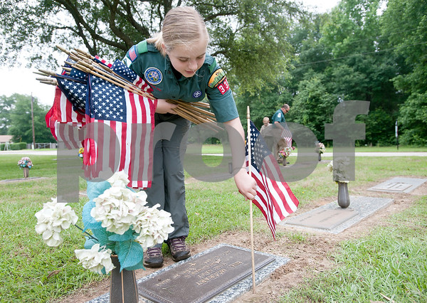 Venture Scout Taylor Rapp, 14, of Tyler, places a flag on a veteran's headstone at Tyler Memorial Funeral Home Cemetery and Mausoleum Saturday morning. Scout troops planted hundreds of American flags on the head stones of veterans Saturday at Tyler Memorial Funeral Home Cemetery and Mausoleum in preparation for Memorial Day Monday. The cemetery will be hosting a Memorial Day service open to the public at 11 a.m.  (photo by Sarah A. Miller/Tyler Morning Telegraph)