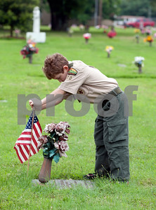 Boy Scout Benjahmin Boynton, 11, of Tyler, places a flag by a veteran's headstone at Tyler Memorial Funeral Home Cemetery and Mausoleum Saturday morning. Scout troops planted hundreds of American flags on the head stones of veterans Saturday at Tyler Memorial Funeral Home Cemetery and Mausoleum in preparation for Memorial Day Monday. The cemetery will be hosting a Memorial Day service open to the public at 11 a.m.  (photo by Sarah A. Miller/Tyler Morning Telegraph)