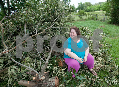"""Joan Pool of Henderson, Texas, sits on a log in a pile of debris outside her home that was destroyed by a falling tree Monday night. The National Weather Service's Shreveport, Louisiana office has confirmed that a tornado did touch down in Rusk county and the city of Henderson Monday evening. """"I have renter's insurance, but it doesn't cover the structure, so what am I going to do?"""" Joan Pool said. Pool lives in a mobile home just off FM 13 with her 21-year-old son Jeffery Cox. While they were home a large tree crashed through the middle of their home, knocking them to the ground.   (photo by Sarah A. Miller/Tyler Morning Telegraph)"""