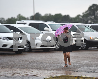 Enedina Felix uses an umbrella as she walks in the rain through the Rose Garden Center parking lot Thursday May 26, 2016 in Tyler.  (Sarah A. Miller/Tyler Morning Telegraph)