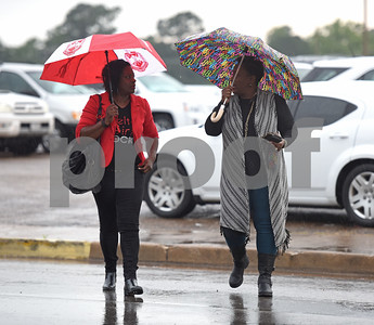 Kendra Tuck and Monica Powell use umbrellas as they walk in the rain through the Rose Garden Center parking lot Thursday May 26, 2016 in Tyler.  (Sarah A. Miller/Tyler Morning Telegraph)