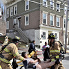 Mike McMahon - The Record, Woman rescued, with her dog on her lap from 2nd floor apartment at a fully involved 2-alarm fire at 554 4th Street in Troy, Wednesday April 16, 2014