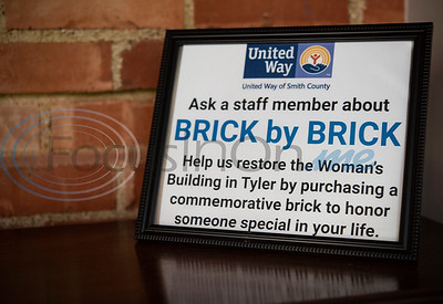Friends, family and former students of Becky Berry surprise her with a namesake brick in the wall at the United Way of Smith County's office at The Tyler Woman's Building on Tuesday May 7, 2019. Berry taught high school for more than 30 years, most of those at Robert E. Lee High School.  The United Way of Smith County's 'Brick by Brick' campaign raises money for the renovation of the building and honors special individuals   (Sarah A. Miller/Tyler Morning Telegraph)