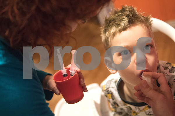 Jessica Ogden feeds Alfie, 8, his seizure medicine after breakfast April 14, 2016.  Jessica's mornings start early as she prepares each of the kids for their daily actives such as school, day care and doctor's appointments.   (Sarah A. Miller/Tyler Morning Telegraph)