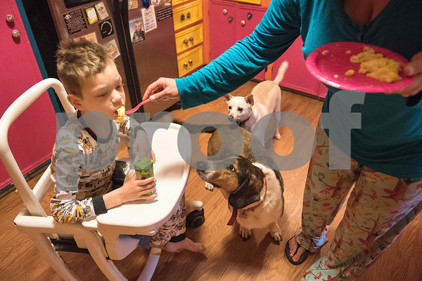Jessica Ogden feeds Alfie, 8, breakfast April 14, 2016.  Jessica's mornings start early as she prepares each of the kids for their daily actives such as school, day care and doctor's appointments.   (Sarah A. Miller/Tyler Morning Telegraph)