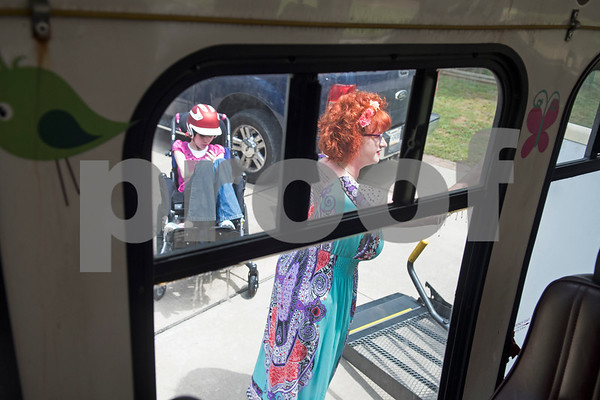 Jessica Ogden lowers the wheelchair lift on her bus to load Lulu so the family could attend Krystal's adult daycare musical performance April 10, 2016.   (Sarah A. Miller/Tyler Morning Telegraph)