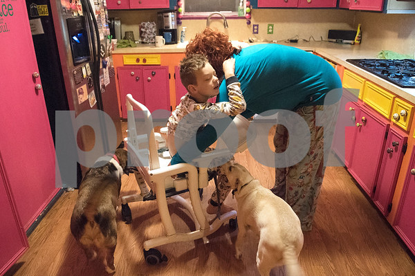 Jessica Ogden puts Alfie, 8, in a highchair for breakfast April 14, 2016.  Jessica's mornings start early as she prepares each of the kids for their daily actives such as school, day care and doctor's appointments.   (Sarah A. Miller/Tyler Morning Telegraph)