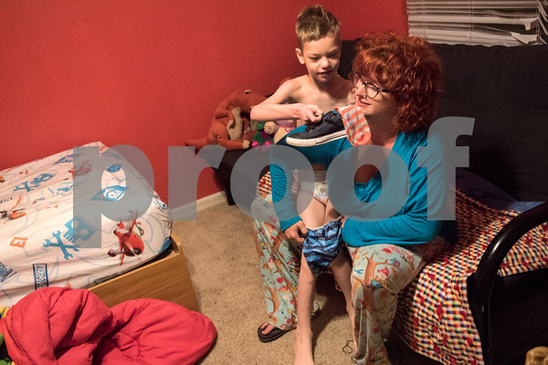 Jessica Ogden dresses Alfie, 8, April 14, 2016.  Jessica's mornings start early as she prepares each of the kids for their daily actives such as school, day care and doctor's appointments.   (Sarah A. Miller/Tyler Morning Telegraph)