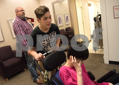 Dalton Ogden, 14, pushes his step sister's wheelchair as they shop at the mall April 16, 2016. The Ogdens have a blended family of five children including three with special needs.  (Sarah A. Miller/Tyler Morning Telegraph)