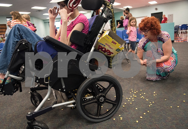 Jessica Ogden cleans up Corn Pops cereal that Lulu spilled while watching Krystal's musical performance at the Boys and Girls Club April 10, 2016. Lulu has special needs and frequent snacks help keep her calm.   (Sarah A. Miller/Tyler Morning Telegraph)