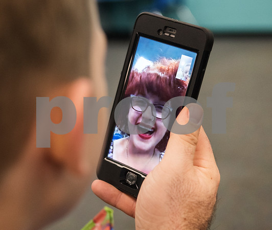 Robert Ogden holds a cell phone so Alfie, 8, can video chat with his mother Jessica Ogden, April 10, 2016. Although the three were sitting next to each other at the time, the video kept Alfie focused as they waited for Krystal's adult daycare musical performance at The Boys and Girls Club.   (Sarah A. Miller/Tyler Morning Telegraph)