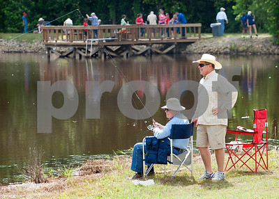 Meadow Lake resident Bill Coleman and his son Hub Coleman of Tyler fish at the Meadow Lake Fishing Derby Friday June 12, 2015. The free event was open to kids and adults of all ages. Prizes were given out to both adult winners and youth winners. Meadow Lake is a retirement community located just south of Tyler in Flint, Texas.    (photo by Sarah A. Miller/Tyler Morning Telegraph)