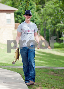 Chase Bonner of Tyler carries a fish he caught to the weigh-in table at the Meadow Lake Fishing Derby Friday June 12, 2015. The free event was open to kids and adults of all ages. Prizes were given out to both adult winners and youth winners. Meadow Lake is a retirement community located just south of Tyler in Flint, Texas.    (photo by Sarah A. Miller/Tyler Morning Telegraph)