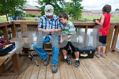 Travis Salter, 10, of Tyler, leans on his grandfather David Bonilla as Bonilla baits the line at the Meadow Lake Fishing Derby Friday June 12, 2015. Pictured at right is Ethan Salter, 9. The free event was open to kids and adults of all ages. Prizes were given out to both adult winners and youth winners. Meadow Lake is a retirement community located just south of Tyler in Flint, Texas.    (photo by Sarah A. Miller/Tyler Morning Telegraph)
