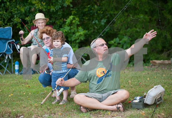 Jackson Ashby, 2, of Flint, fishes with his grandmother Lolli Ashby and grandfather Rick Ashby at the Meadow Lake Fishing Derby Friday June 12, 2015. The free event was open to kids and adults of all ages. Prizes were given out to both adult winners and youth winners. Meadow Lake is a retirement community located just south of Tyler in Flint, Texas.    (photo by Sarah A. Miller/Tyler Morning Telegraph)