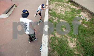 Coach Sergio Chavez of Tyler, left, instructs Caleb Carpenter, 12, of Tyler, on how to do a kick flip on his skateboard Saturday during Training Day at Noble E. Young Skatepark in Tyler. Training Day was a fundraising event put on by the East Texas Skatepark Association to raise money for repairs to Noble E. Young Skatepark and to help people learn to skateboard. Beginning skateboarders paid $20 for one-on-one lessons from local coaches from 11 a.m. to 2 p.m. Basic skills as well as tricks and different riding styles were taught. East Texas Skatepark Association's next event will be a skateboard competition June 27 at noon. Visit www.facebook.com/savenobleskatepark for more information.  (photo by Sarah A. Miller/Tyler Morning Telegraph)