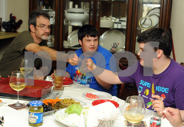 photo by Sarah A. Miller/Tyler Morning Telegraph  Jay Newman of Tyler passes an pickle slice to his son Cody, 17, during a social dinner with neighbors at their house June 3, 2014. Newman is a single father raising his two sons who both have autism.