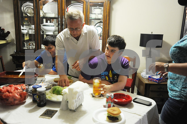 photo by Sarah A. Miller/Tyler Morning Telegraph  Neighbor Brian Smith reaches between brothers Kyle, 21, and Cody Newman, 17, for hamburger condiments during a social dinner at the Newman's house Memorial Day. Their father Jay Newman likes them to meet people and be social.