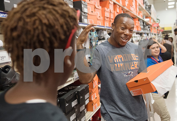 NFL player Teddy Williams reacts to the shoes Payton Campbell, 13, picked out during a shopping spree Williams hosted at Academy Sports + Outdoors in Tyler on Friday June 15, 2018. Teddy Williams is a John Tyler High School alum. He is holding his free Fast Like Teddy Speed & Agility Camp hosted by Christus Trinity Mother Frances Health System on Saturday June 16 at John Tyler High School. Four camp participants won a $100 shopping spree.   (Sarah A. Miller/Tyler Morning Telegraph)
