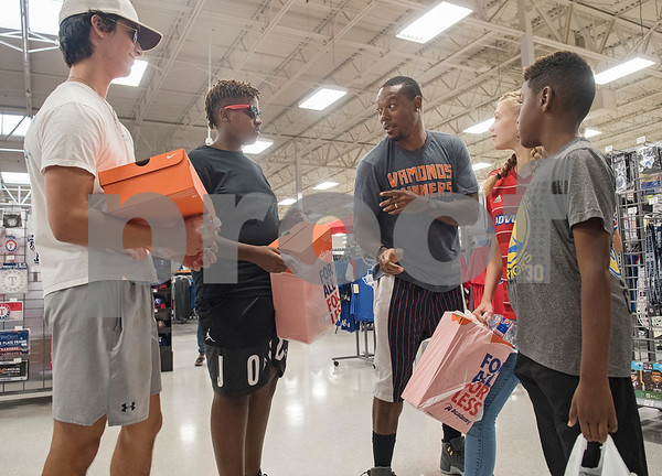 NFL player Teddy Williams, center, talks to four children who participated in a shopping spree he hosted at Academy Sports + Outdoors in Tyler on Friday June 15, 2018. Williams is a John Tyler High School alum. He is holding his free Fast Like Teddy Speed & Agility Camp hosted by Christus Trinity Mother Frances Health System on Saturday June 16 at John Tyler High School. Four camp participants won a $100 shopping spree. Pictured from left: Matthew Muehe, 15, Payton Campbell, 13, Teddy Williams, Sofie Williams, 12, and J'Mhir Ford, 9.  (Sarah A. Miller/Tyler Morning Telegraph)