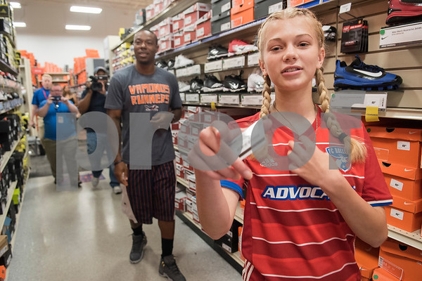 Sofie Williams, 12, holds her $100 gift card in her hand as NFL player Teddy Williams follows her helping her shop for soccer cleats during a shopping spree the NFK player hosted at Academy Sports + Outdoors in Tyler on Friday June 15, 2018. Teddy Williams is a John Tyler High School alum. He is holding his free Fast Like Teddy Speed & Agility Camp hosted by Christus Trinity Mother Frances Health System on Saturday June 16 at John Tyler High School. Four camp participants won a $100 shopping spree.   (Sarah A. Miller/Tyler Morning Telegraph)