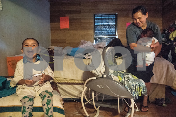 Elias Garcia, 3, smiles while playing a video game as his mother Demetria Garcia picks up her youngest child, 2-month-old Alonso, on Monday June 18, 2018 in their home that is being remodeled this week by volunteers from Marvin United Methodist Church's Mission Week ministry. The small home for the family of eight was 480 square feet but will gain an additional 380 square feet with the addition of a two bedrooms.   (Sarah A. Miller/Tyler Morning Telegraph)